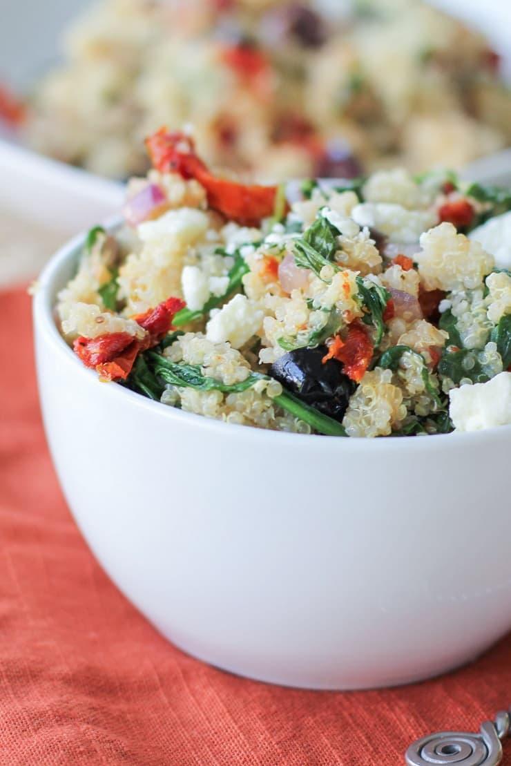 Mediterranean Quinoa Salad with spinach, kalamata olives, sun-dried tomatoes, feta, and lemon vinaigrette - a healthy vegetarian meal or side dish!