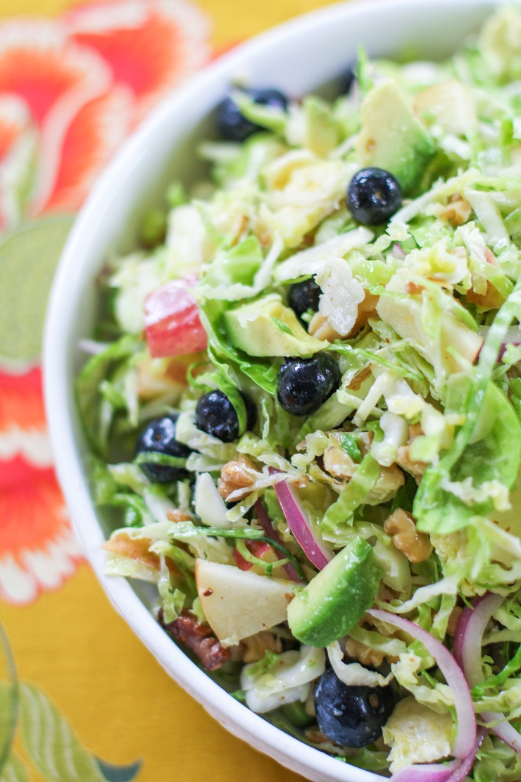Shaved Brussels Sprouts Salad with avocado, apple, red onion, blueberries, walnuts, and citrus dressing | TheRoastedRoot.net #healthy #salad #sidedish #glutenfree #paleo #vegan