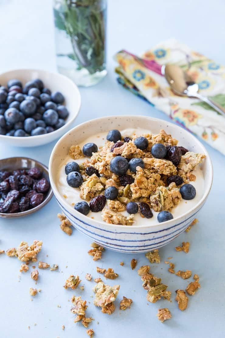 Grain-Free Paleo Granola made with nuts and seeds. This refined sugar-free recipe yields huge granola clusters and is super crunchy and delicious for breakfast