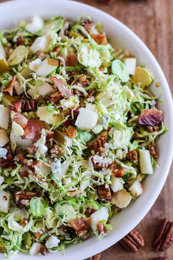 Brussel Sprout Chopped Salad with bacon, pears, candied pecans, blue cheese, and maple-bacon vinaigrette | TheRoastedRoot.com