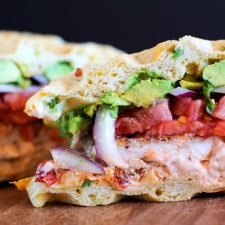 Gluten Free Jalapeño Cheddar Bacon Waffle Sandwiches with gluten-free fried chicken, mashed avocado, and chipotle yogurt sauce