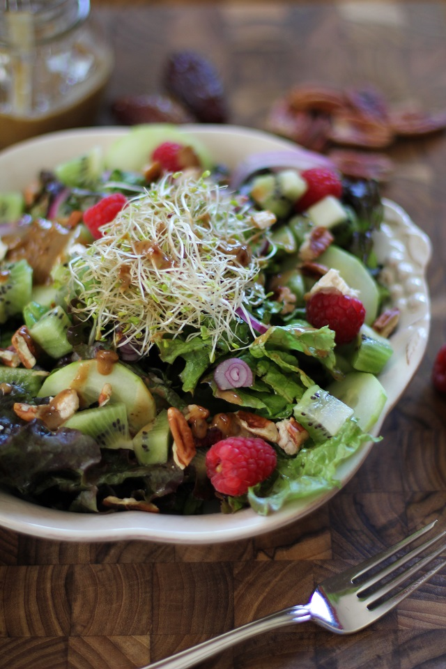 Spring Green Salad with kiwi, raspberries, cucumbers, sprouts, pecans, and date-balsamic vinaigrette | theroastedroot.net #vegetarian #recipe #healthy