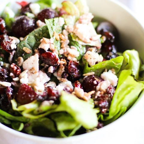 Spinach Salad with sunflower seeds, dried cranberries, grapes, feta cheese, and raspberry vinaigrette | TheRoastedRoot.net #healthy #recipe #vegetarian