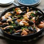 Seafood Paella with chicken, sausage, shrimp, and mussels - a delicious tapas recipe to serve to guests | TheRoastedRoot.net #healthy #dinner #recipe #spanish #glutenfree