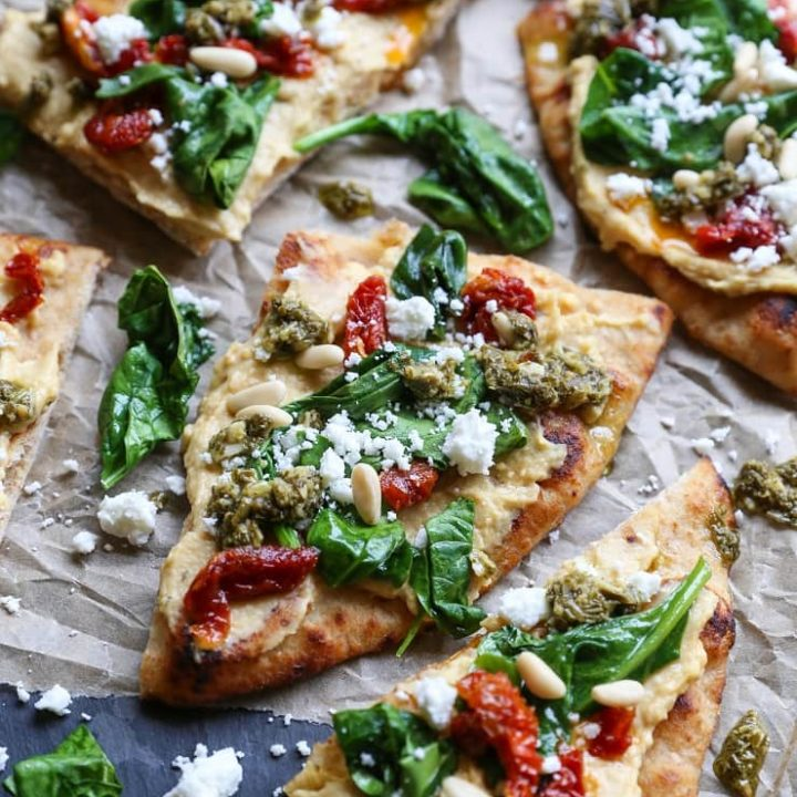 Hummus Flatbread with Sun-Dried Tomatoes, Spinach, Pesto, and Feta Cheese - a delicious healthy appetizer or meal