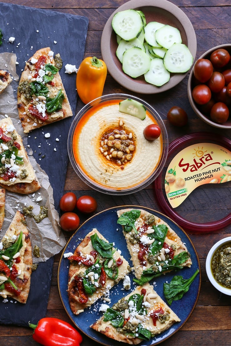 Hummus Flatbread with Sun-Dried Tomatoes, Spinach, and Pesto- an easy appetizer or snack packed with nutrition.