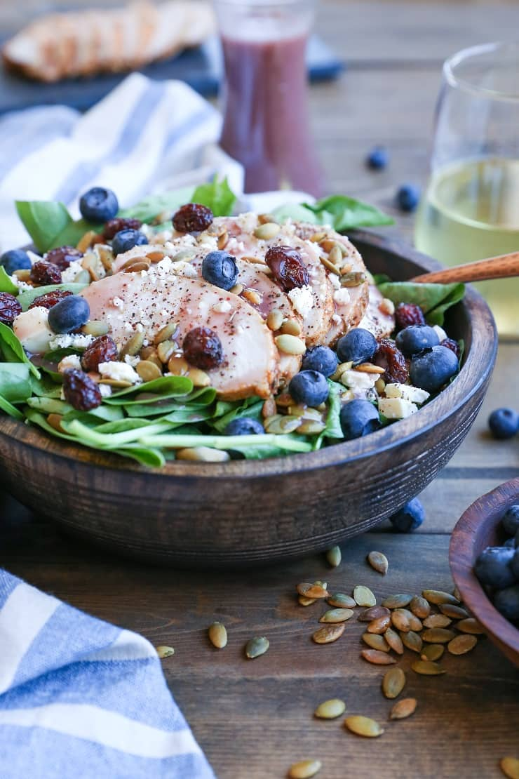 Baked Chicken Spinach Salad with dried cranberries, blueberries, feta cheese, roasted pumpkin seeds, and raspberry vinaigrette - a healthy lunch or dinner recipe