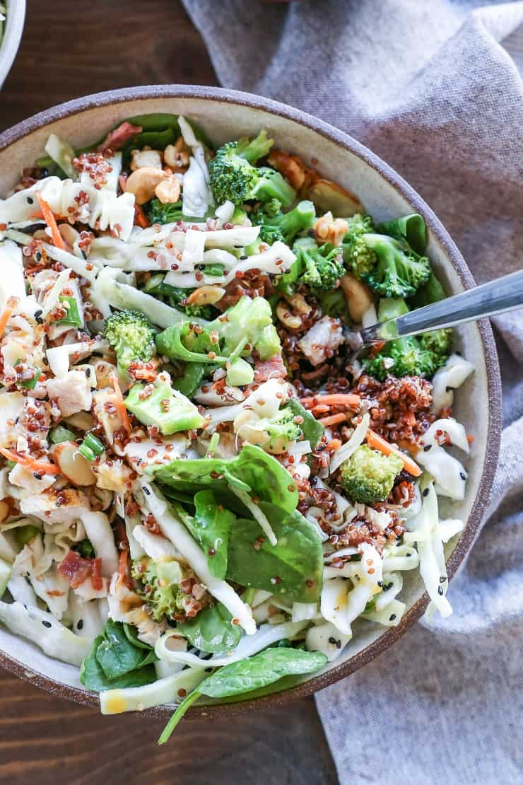 Detox spinach salad with quinoa, broccoli, cabbage, cashews, bacon, dried cranberries, and orange-ginger dressing #paleo #healthy #saladrecipe