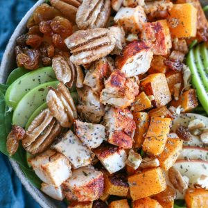 Roasted Butternut Squash Spinach Salad with apples, pecans,golden raisins, and cinnamon maple cider vinaigrette. A healthy whole30 paleo meal!