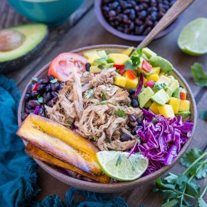 Crock Pot Carnitas Burrito Bowls with mango salsa, black beans, fried plantains, and shredded cabbage