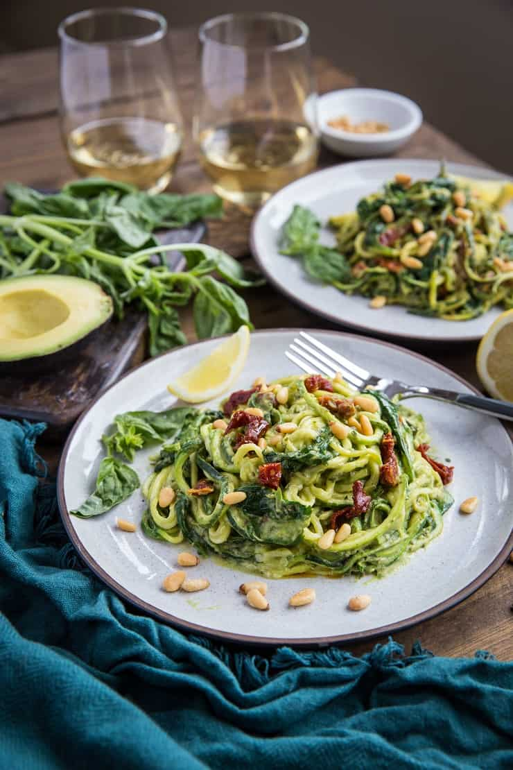 Avocado Pesto Zoodles with Sun-Dried Tomatoes, Spinach, and Pine Nuts - this gluten-free, vegan, paleo dinner recipe only requires about 30 minutes to make.
