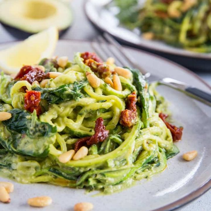 Avocado Pesto Zoodles with Sun-Dried Tomatoes, Spinach, and pine nuts. These creamy zucchini noodles are vegan, paleo, healthy, and super easy to make