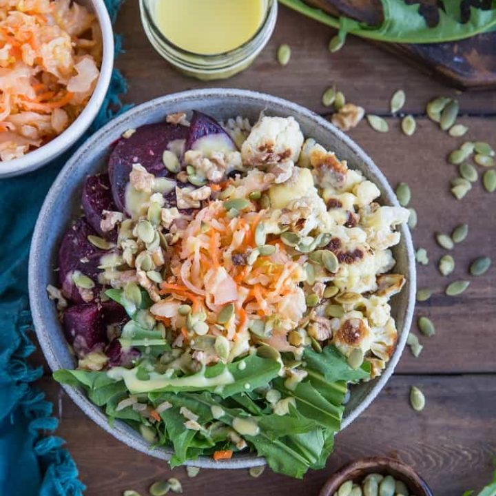 Gut Healthy Probiotic Power Bowls with roasted beets, cauliflower, dandelion greens, brown rice, sauerkraut, and orange dressing. These nutrient-rich bowls are amazing for maintaining a healthy gut.