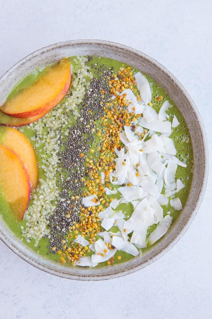 Ginger Peach Smoothie Bowl made banana-free with cauliflower and orange juice. Topped with flaked coconut, bee pollen, chia seeds, hemp seeds and peaches for a real good time. Paleo and delicious! | TheRoastedRoot.net