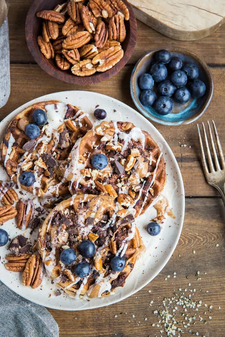 Paleo Chocolate Pecan Waffles with almond butter, coconut butter, and blueberries. This easy waffle recipe is clean and delicious!