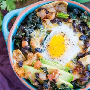 Baked Huevos Rancheros - a unique spin on the traditional Mexican breakfast with black beans, corn tortillas, salsa, avocado, kale, and cheese
