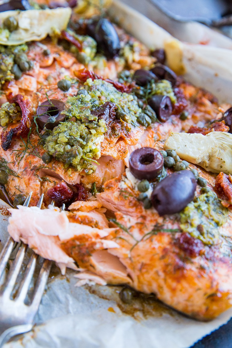 Mediterranean Salmon in Parchment Paper - paleo, keto, low-carb, amazingly flavorful dinner recipe! This salmon with pesto, kalamata olives, capers, sun-dried tomatoes, and artichoke hearts is an epic crowd pleaser!