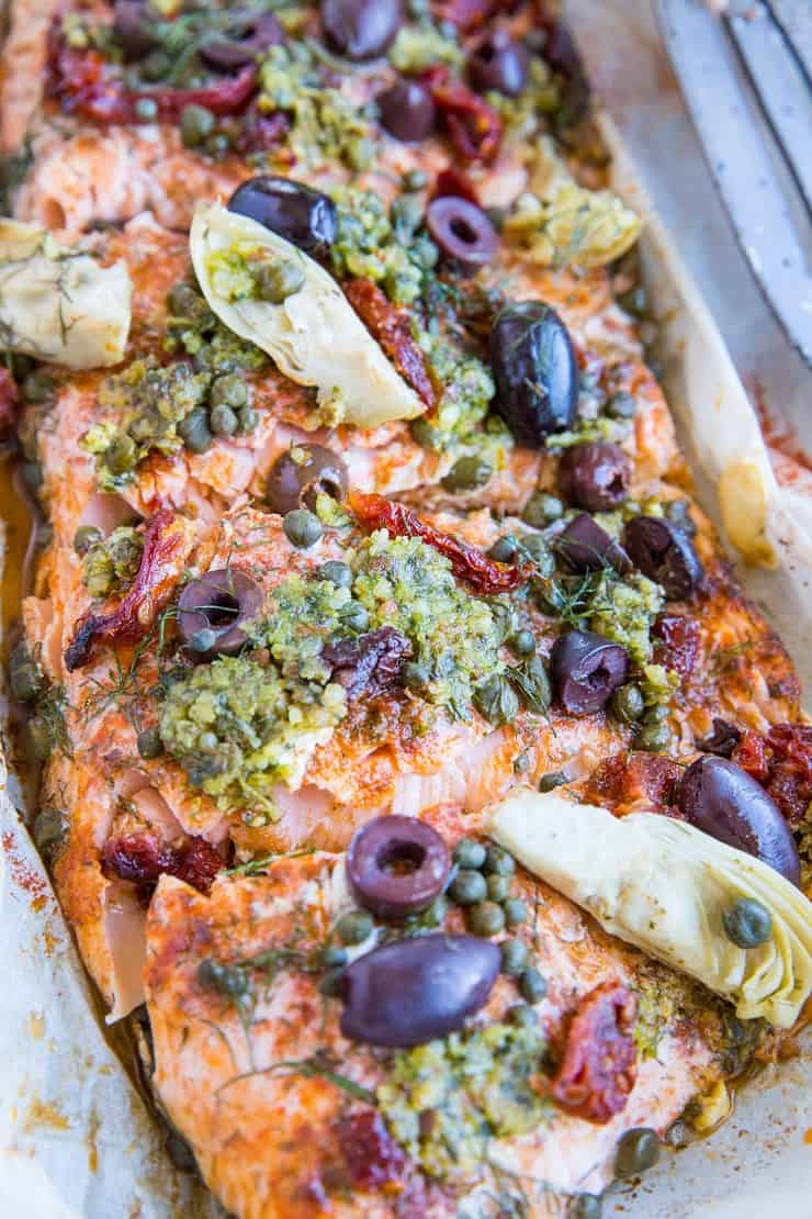 Mediterranean Salmon in Parchment Paper with sun-dried tomatoes, kalamata olives, dill, capers, and artichoke hearts. This easy dinner recipe is paleo, keto, and packed with flavor!