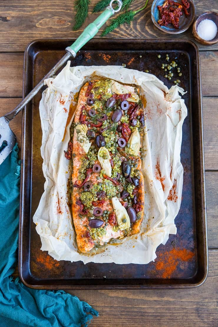 Mediterranean Salmon in Parchment Paper (a.k.a. fish en papillote) with sun-dried tomatoes, kalamata olives, dill, capers, and artichoke hearts. This easy dinner recipe is paleo, keto, and packed with flavor!