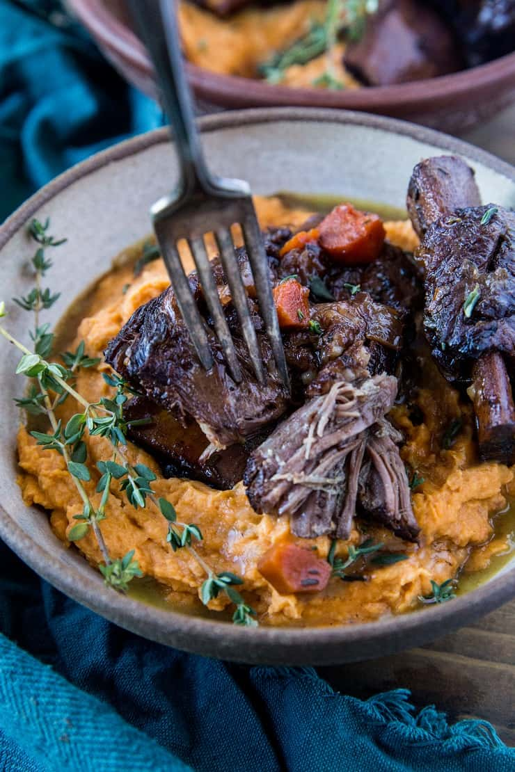 Instant Pot Short Ribs made paleo-friendly with tart cherry juice. Serve them atop mashed sweet potatoes for a delicious complete meal. | TheRoastedRoot.com #grainfree #glutenfree #healthyrecipe