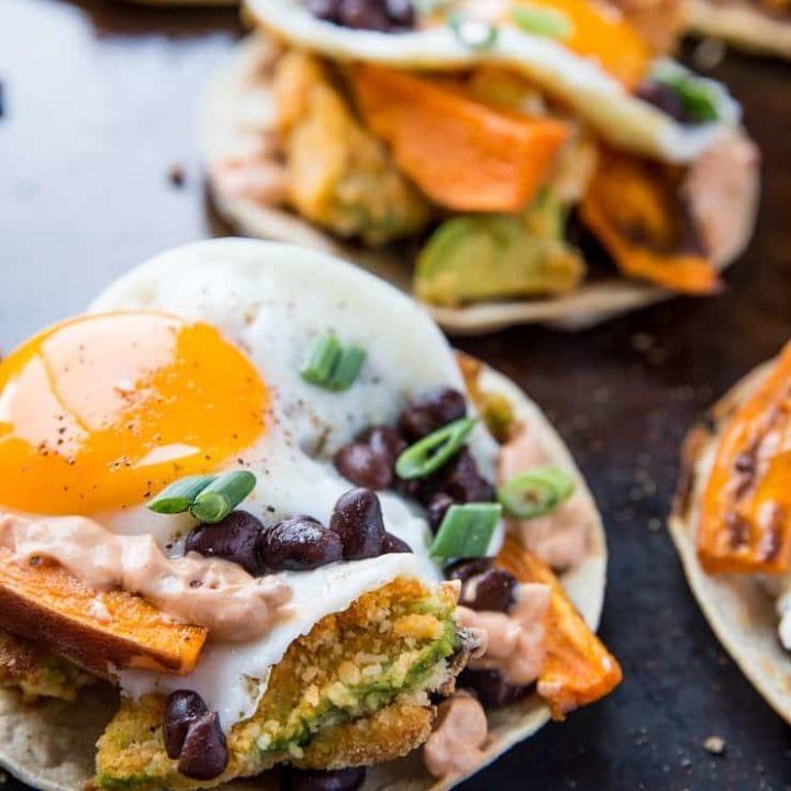Crispy Avocado Breakfast Tacos with roasted sweet potato, cauliflower, black beans, eggs, and chipotle sauce. A healthy brunch recipe | TheRoastedRoot.net #glutenfree #breakfast
