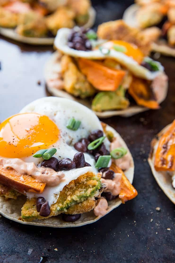 Crispy Avocado Breakfast Tacos with roasted sweet potato, cauliflower, black beans, eggs, and chipotle sauce. A healthy brunch recipe | TheRoastedRoot.net #glutenfree #breakfast