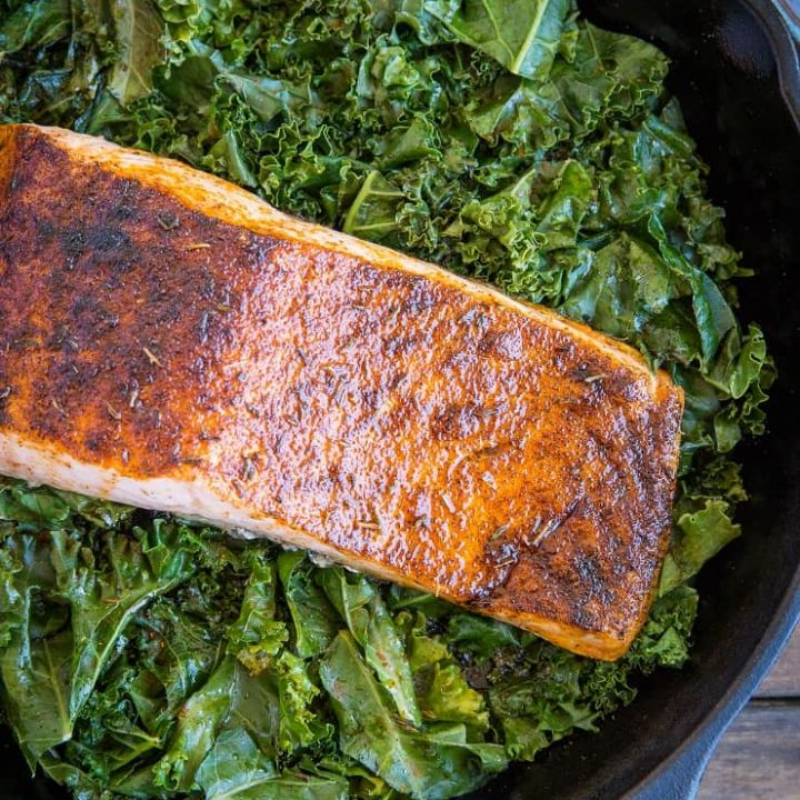 Blackened Salmon with Garlicky Cajun Kale - a healthy low-carb, keto dinner recipe from the cookbook, The Quintessential Kale Cookbook by Julia Mueller | TheRoastedRoot.net