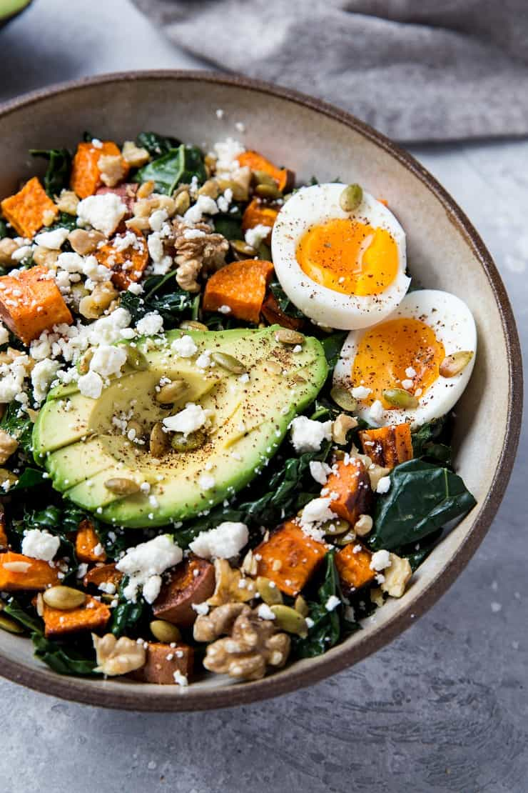 Roasted Sweet Potato Kale Salad with Avocado, Jammy Egg, Pumpkin Seeds, and Walnuts. A filling and nutritious dinner salad   TheRoastedRoot.net