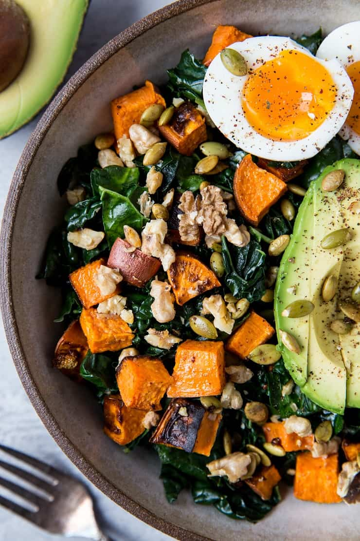 Roasted Sweet Potato Kale Salad with Avocado, Jammy Egg, Pumpkin Seeds, and Walnuts. A filling and nutritious dinner salad | TheRoastedRoot.net
