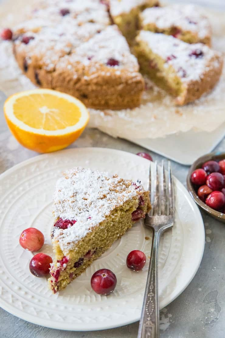 plate with a slice of cranberry orange cake with a fork and fresh cranberries