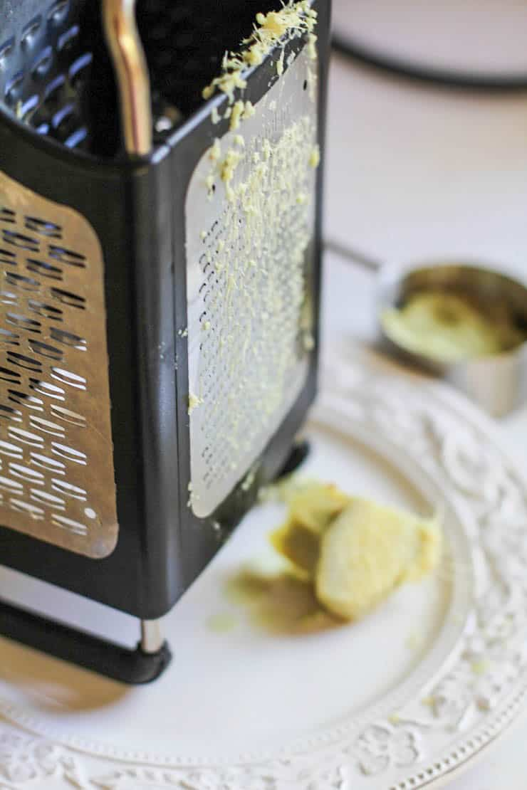 Box grater on a plate with fresh ginger grated on it