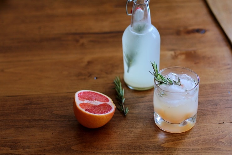 A bottle and a glass of grapefruit rosemary ginger beer sitting on a table with half a grapefruit and sprigs of rosemary
