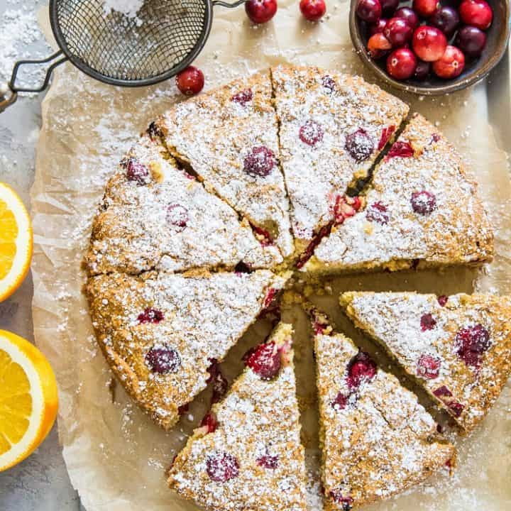 grain-free cranberry orange cake on parchment paper on top of a baking sheet, sprinkled with powdered sugar with fresh cranberries and oranges next to the cake