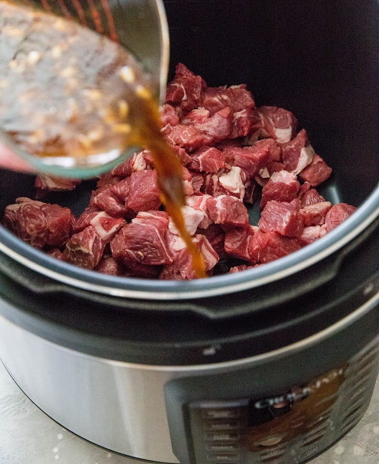 Pour broth into the pressure cooker with the beef