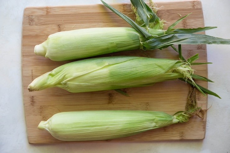 three ears of corn on a wooden cutting board