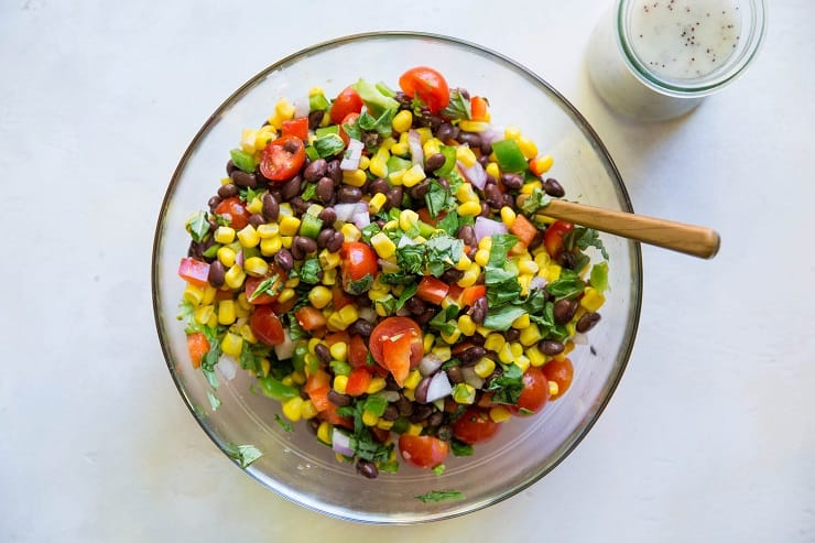 black bean corn salad ingredients in a mixing bowl with lemon poppy seed dressing on the side