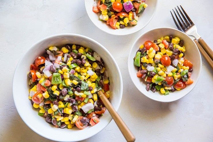 one large bowl and two small bowls of black bean corn salad with two forks on the side on a white backdrop