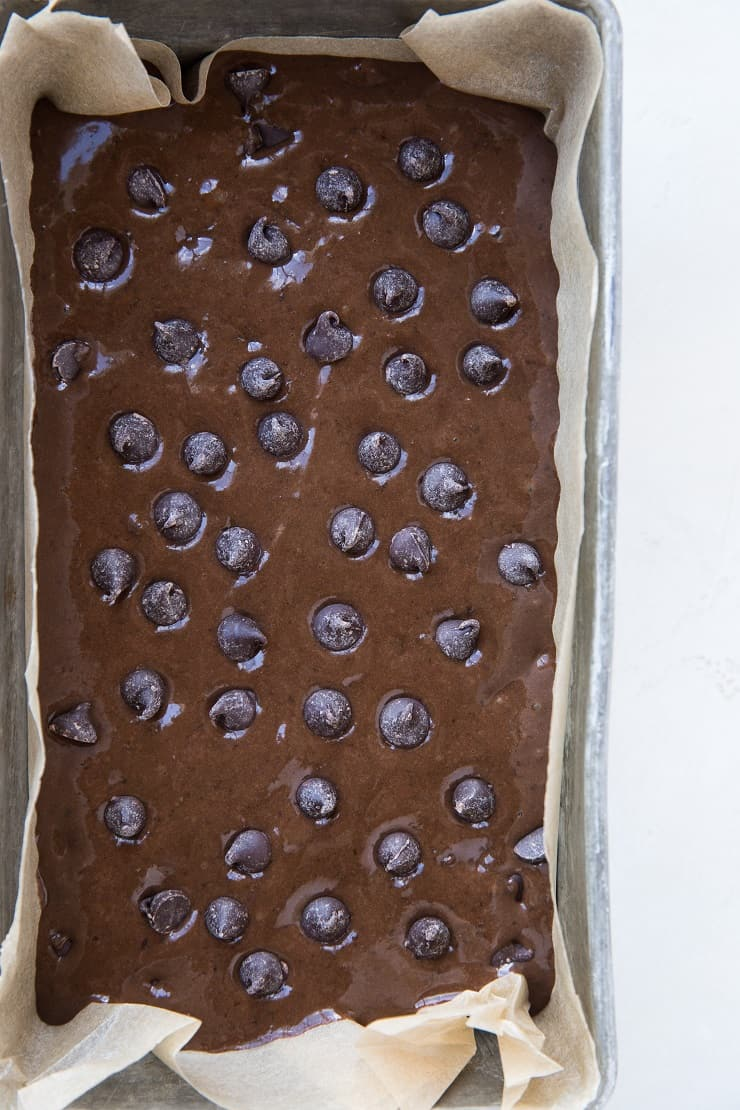 Black bean banana bread batter in a loaf pan with chocolate chips sprinkled on top