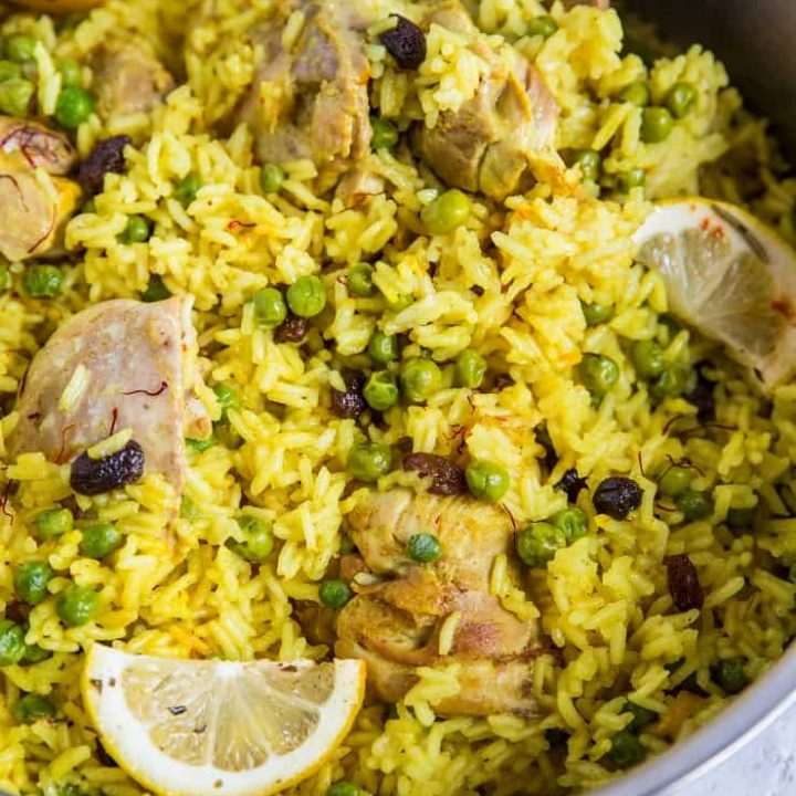 Aromatic Saffron Chicken with Coconut Rice in a large skillet with slices of lemon