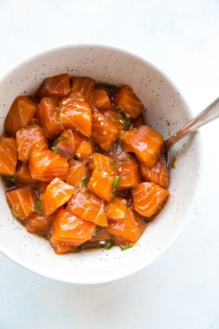 Bowl of salmon poke with a spoon in it on a white surface