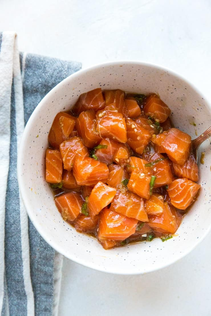 Bowl of salmon poke with spoon and blue napkin on white surface