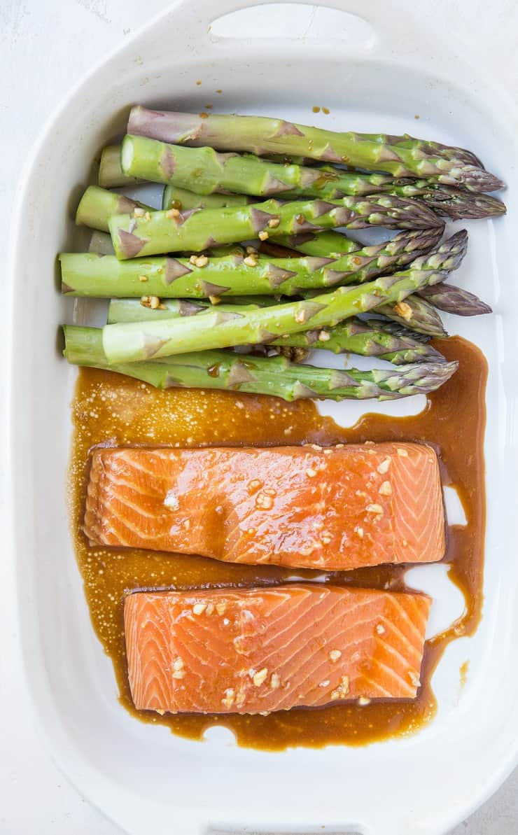 Raw salmon and asparagus in a casserole dish with asian marinade
