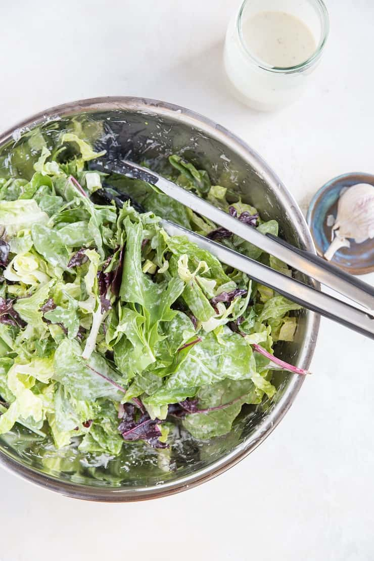 Large Caesar Salad in a mixing bowl with caesar dressing