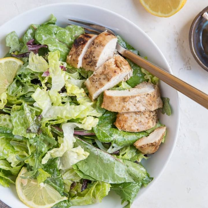 Balsamic Baked Chicken Caesar Salad in a bowl with a napkin and half a lemon