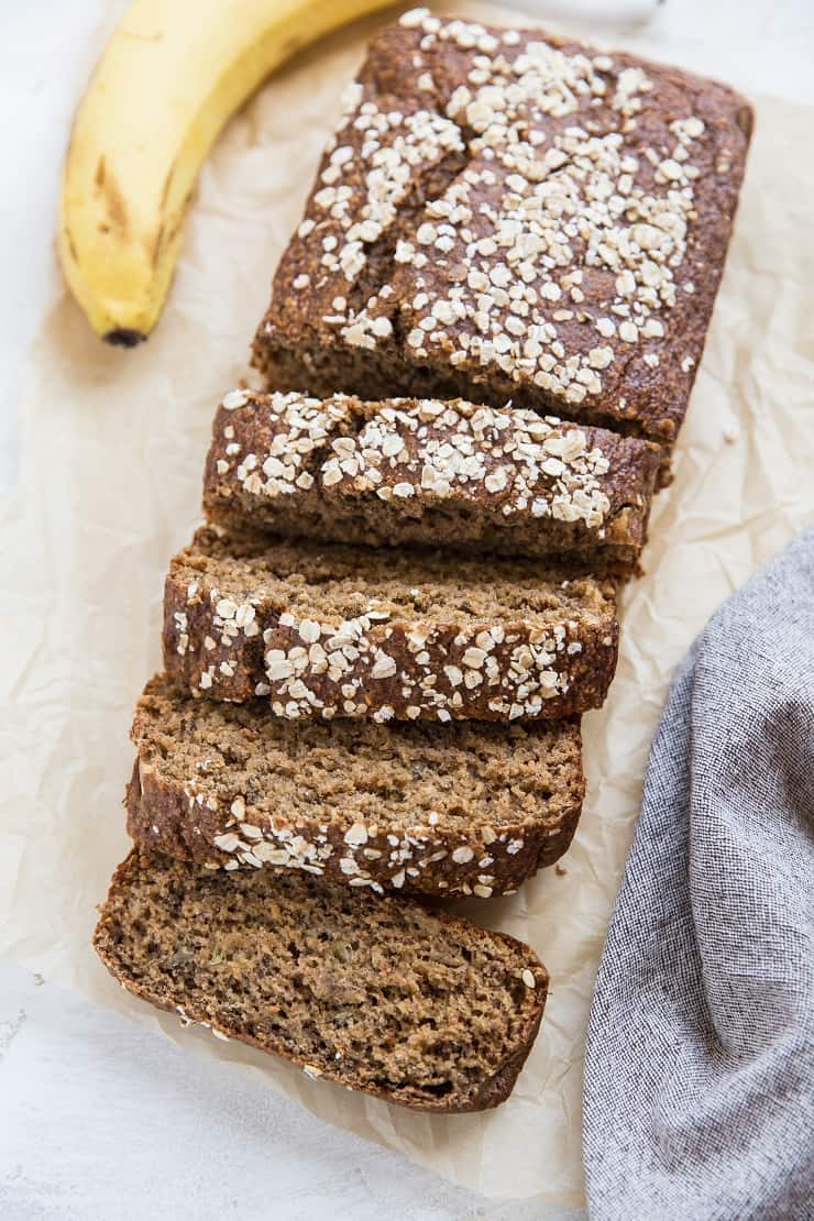 Oatmeal Banana Bread on parchment paper with a napkin and a banana
