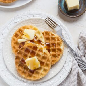 top down photo of two plates of sourdough waffles with butter and honey