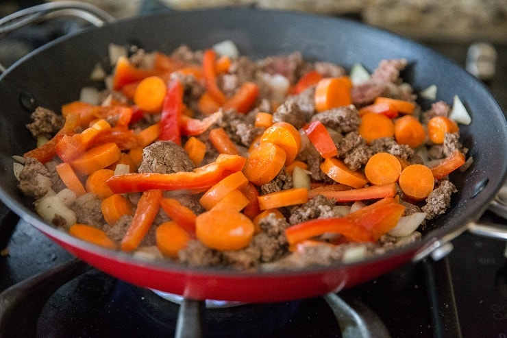 beef and vegetables cooking in a skillet