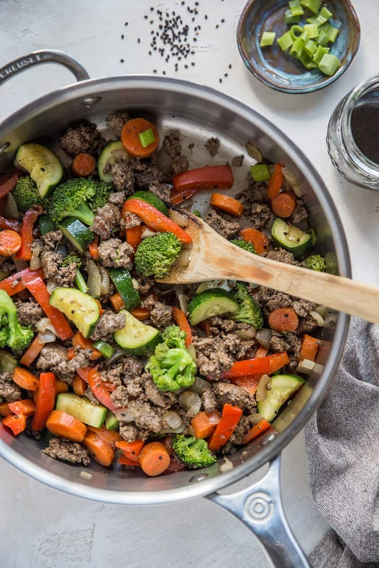30-Minute Teriyaki Beef Skillet with Vegetables sitting on a white backdrop with jar of teriyaki sauce and a wooden spoon