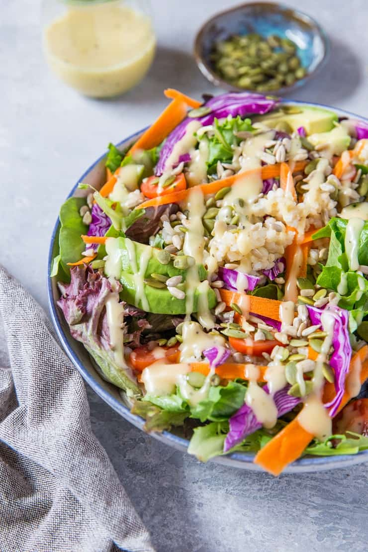 A really great summer salad recipe with greens, carrots, cabbage, avocado, brown rice and homemade dressing