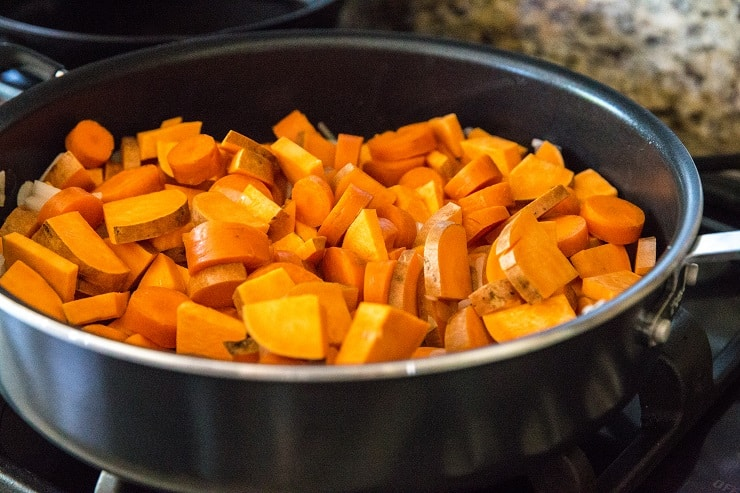 Sweet potatoes, carrots, and onion in a large skillet